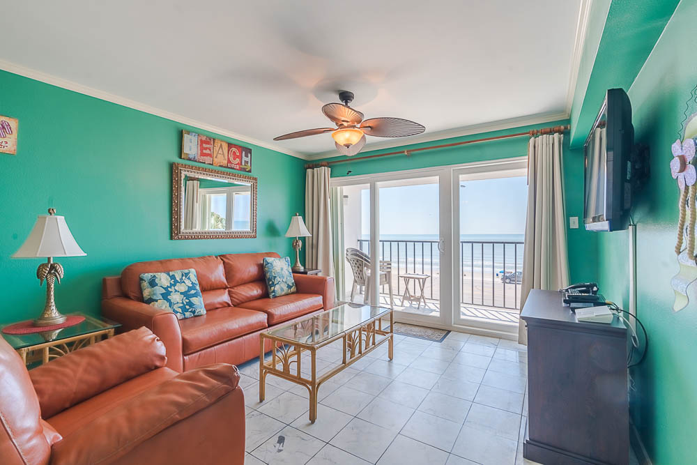 Galveston Texas vacation rental condo living room area with ocean front view, large patio doors, tile floors, and balcony.