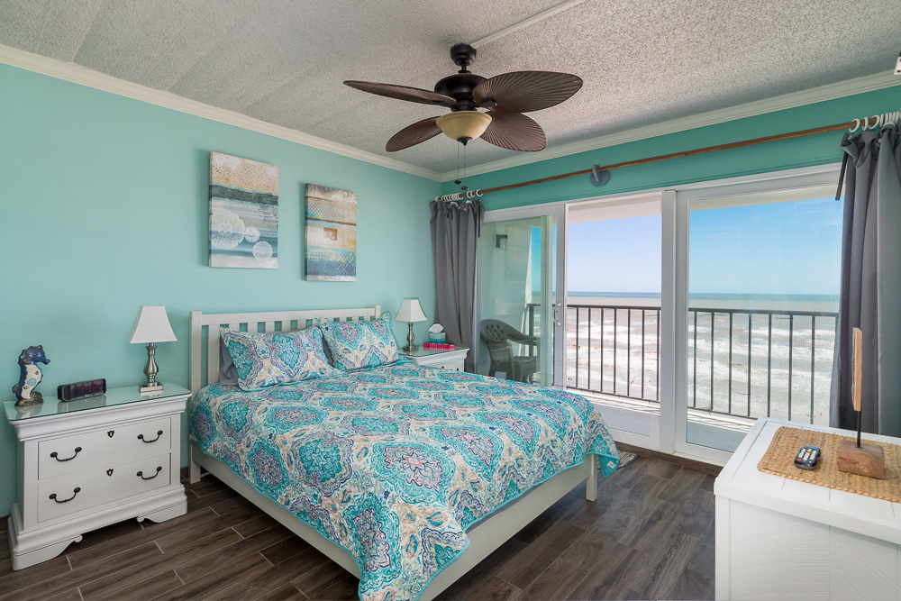 Galveston Condo Rentals On The Seawall with ocean front view featuring bright colors, queen size bed, and large patio doors to balcony.