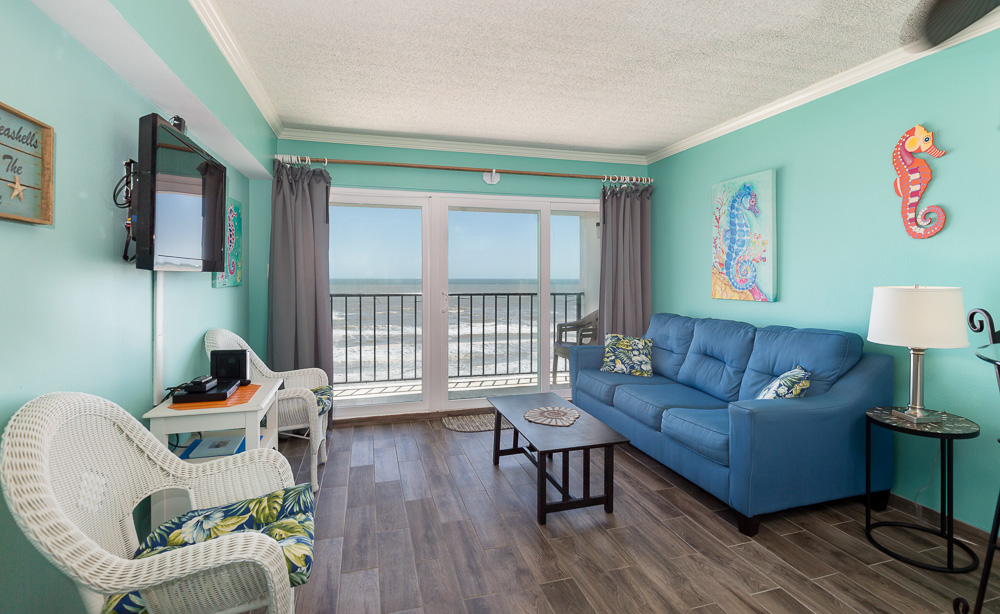 Galveston Texas vacation rental condo on seawall featuring view from large brightly colored living room, patio windows to balcony and oceanfront view.