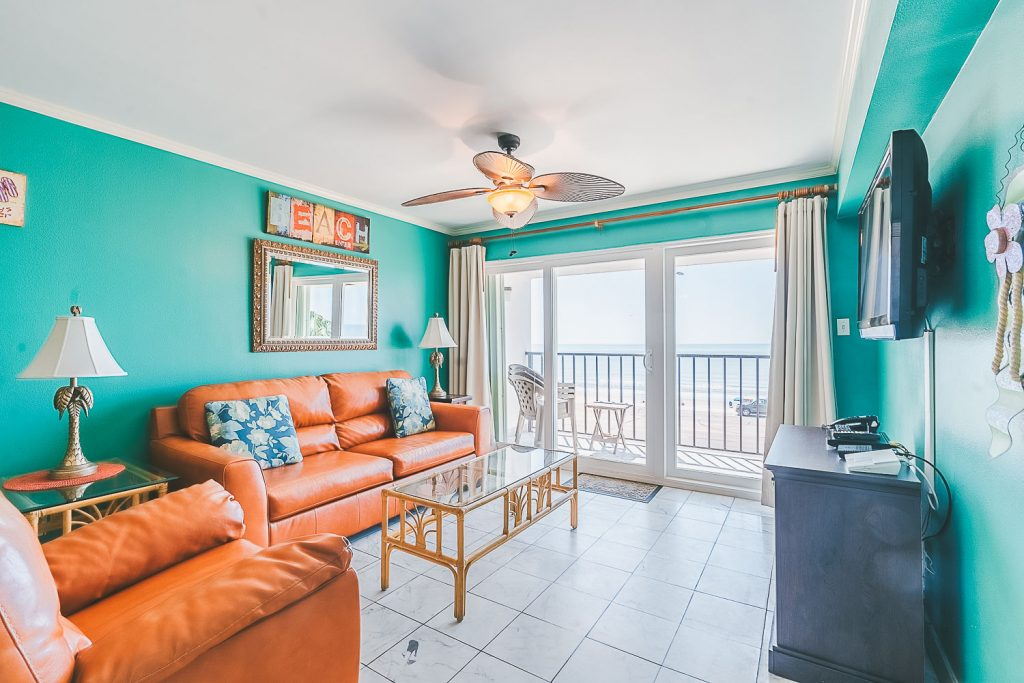 Galveston Texas vacation rental condo on seawall living area with tiled floors and large patio glass doors leading to balcony with ocean front view.
