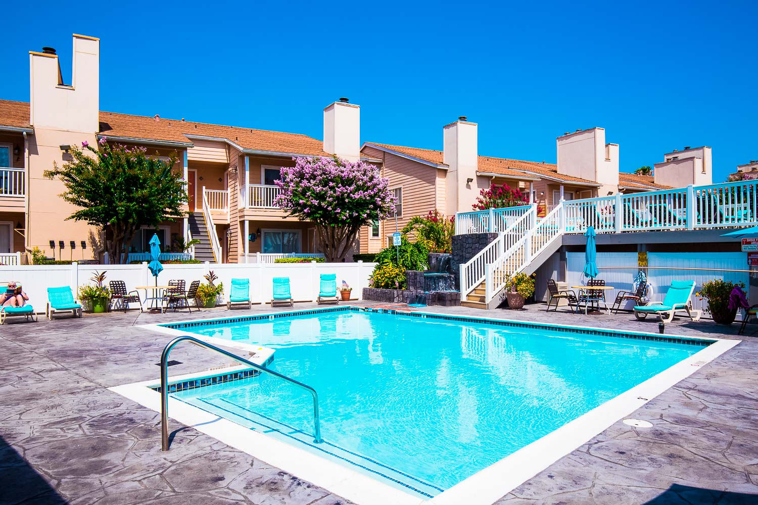 Galveston Texas vacation rental condo on seawall condo landscaping and view of pool, lounge chairs, and condo balconies